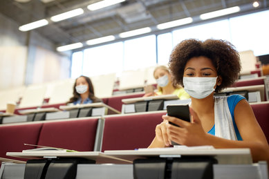 Socially distanced masked college students in classroom during COVID-19 pandemic