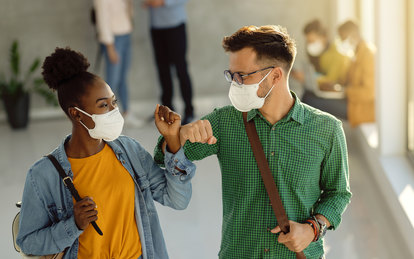 College students with masks elbow bump in hallway